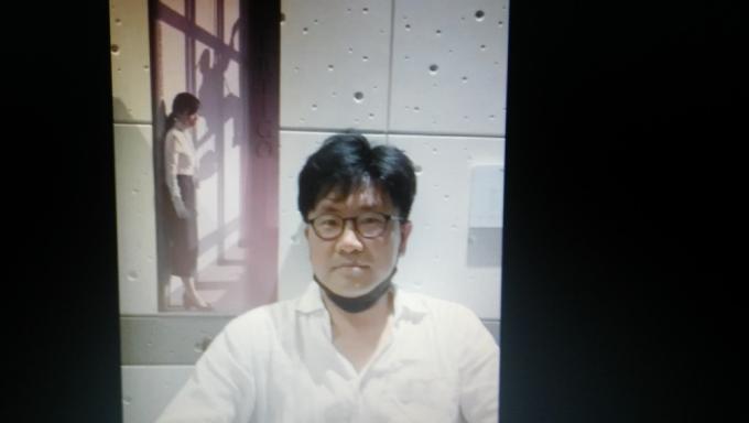 Il regista Jeon Gye-soo davanti alla locandina del film